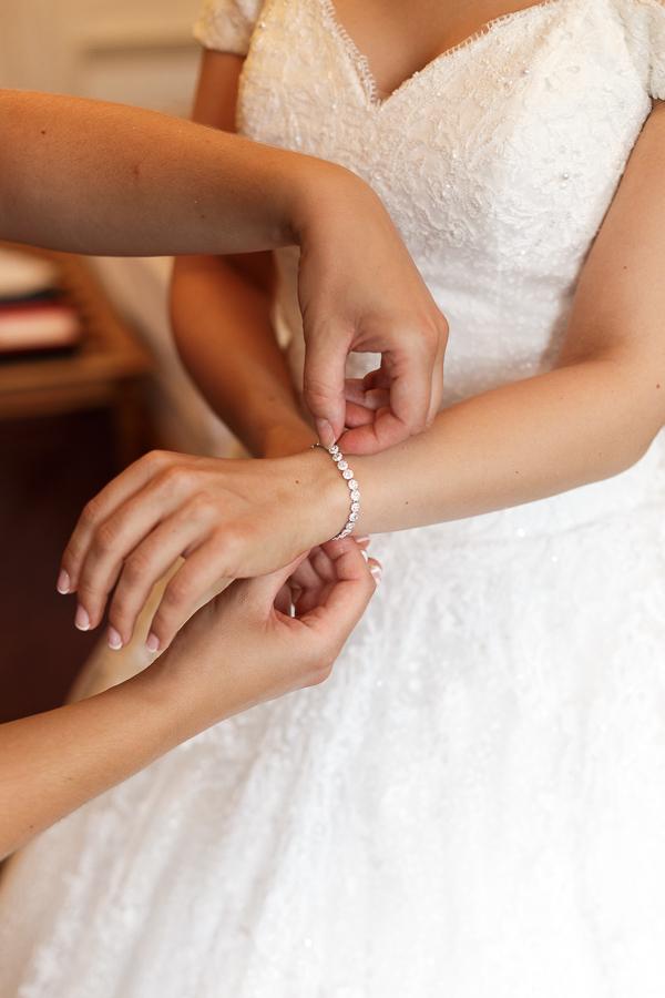 La mariée se fait aider lors de l'habillage et le choix des bijoux