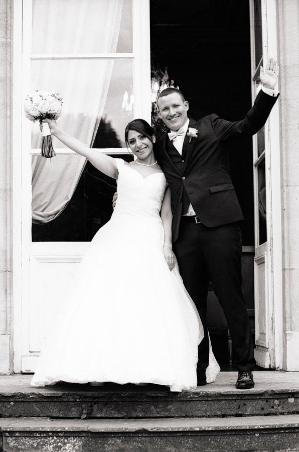 Photographie argentique du couple marié tout sourire devant le château de La Motte Fénelon