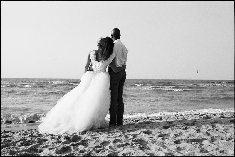 Day After à la plage De Haan Le Coq littoral belge portrait mariés de dos en noir et blanc photographe mariage Nord