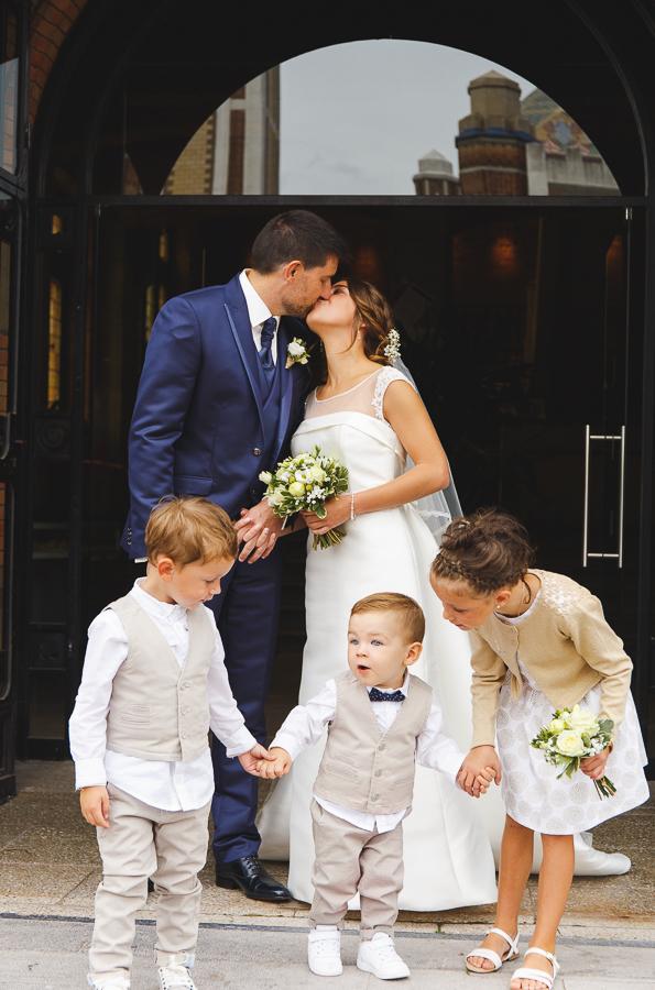 bisou couple fraîchement marié avec enfants d'honneur devant mairie de Comines photographe mariage famille Nord Lille Douai Arras