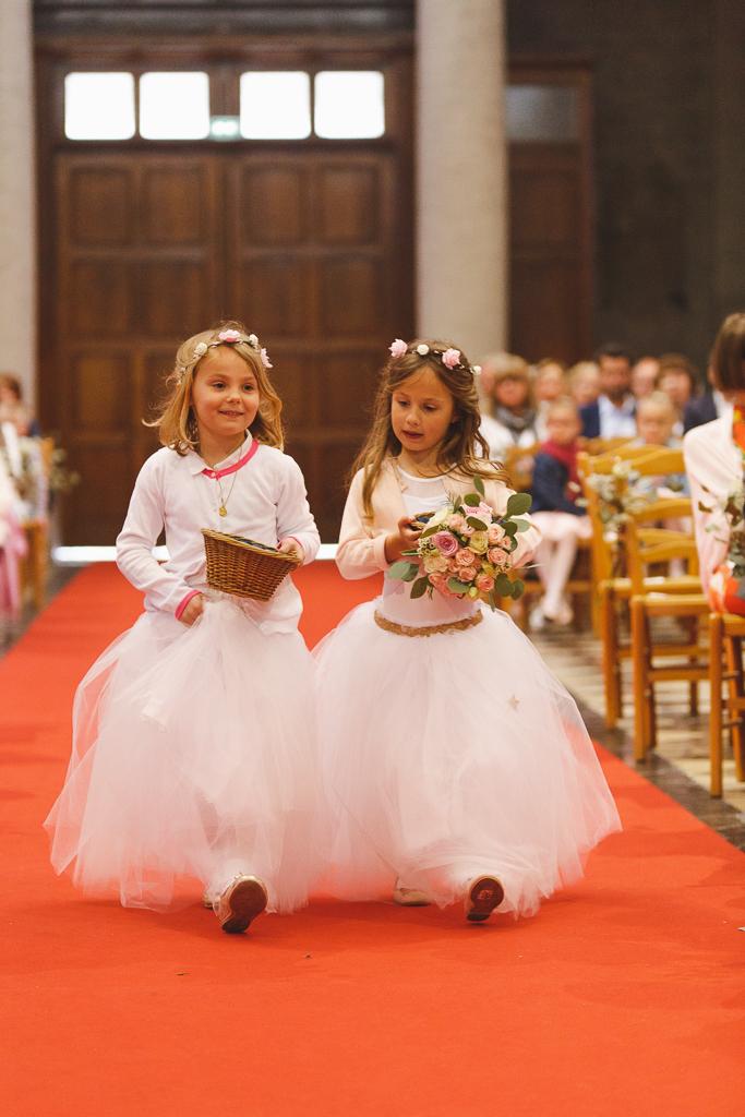 deux filles d'honneur tenue de cérémonie en tulle marche sur tapis rouge église panier en osier et bouquet à la main Fred Laurent photographe mariage