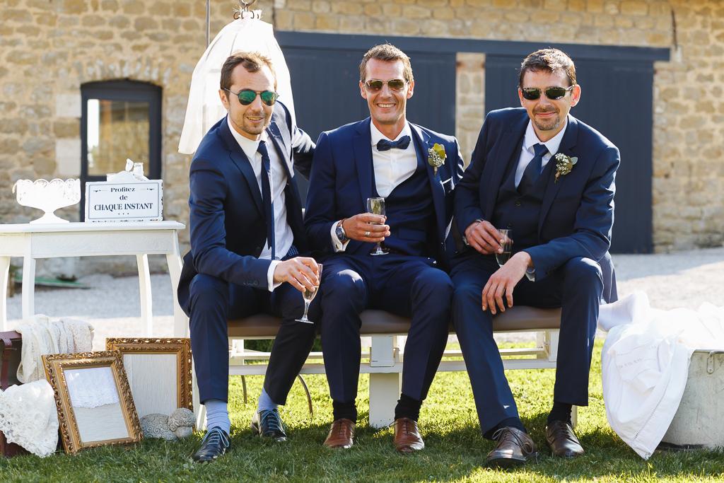 marié et deux invités tous en costume bleu assis sur banc vin d'honneur écriteau photobooth Profitez de chaque instant