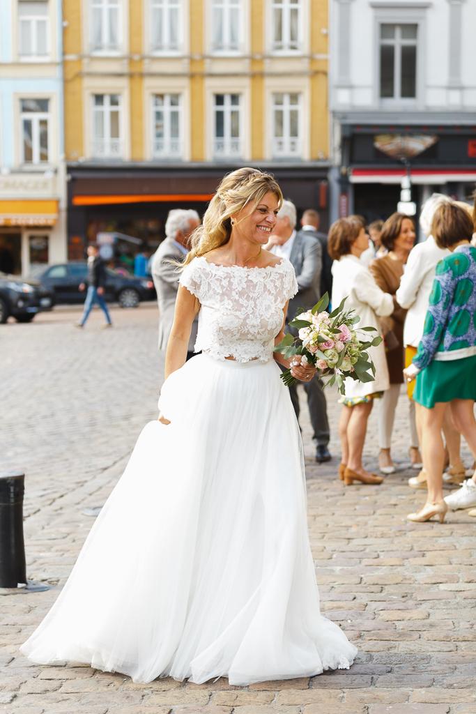 mariée sur parvis église Saint Nicolas Boulogne sur Mer en robe deux pièces haut dentelle motif floral et jupe longue
