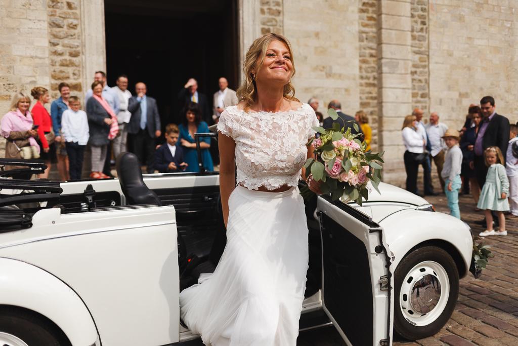mariée sortant de Coccinelle blanche devant église Boulogne sur Mer bouquet pastel roses eucalyptus à la main