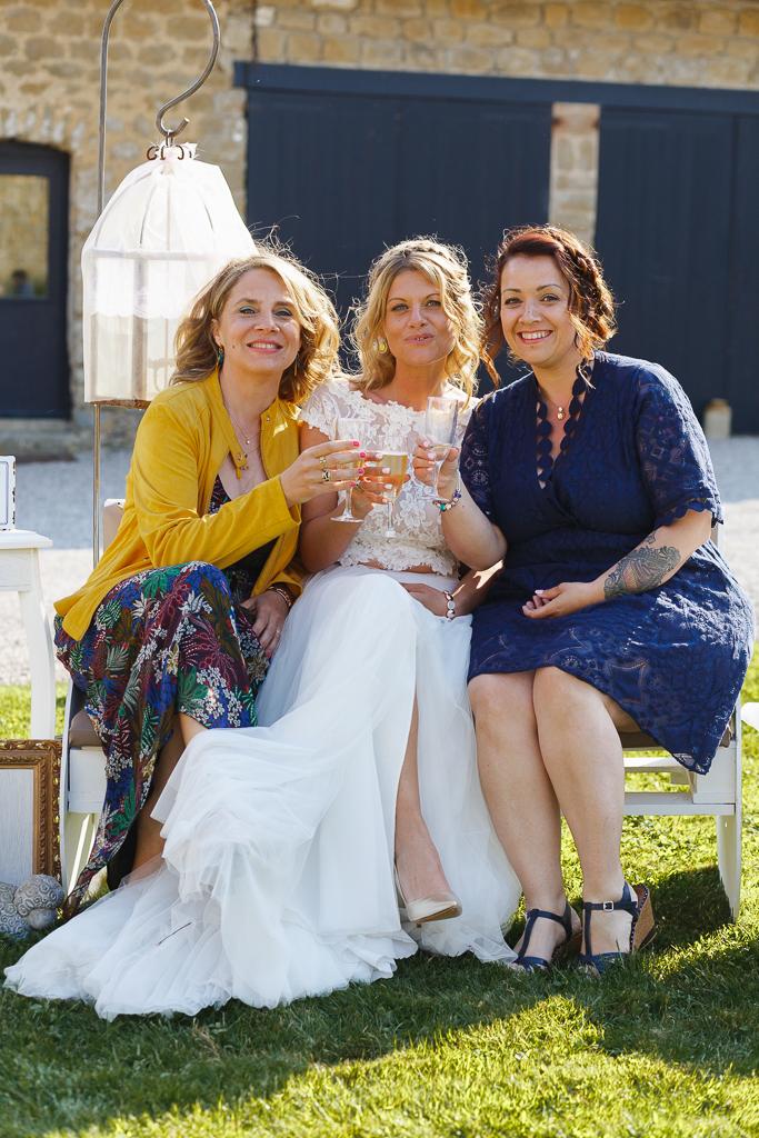 Mariage bucolique à La Magreville de Bellebrune la mariée et ses témoins assises sur un banc pendant les portraits de groupes