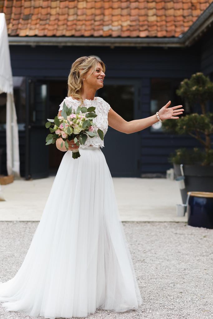 mariée vêtue d'un crop top dentelle fleurie et d'une jupe longue avec son bouquet Mariage bucolique à La Magreville