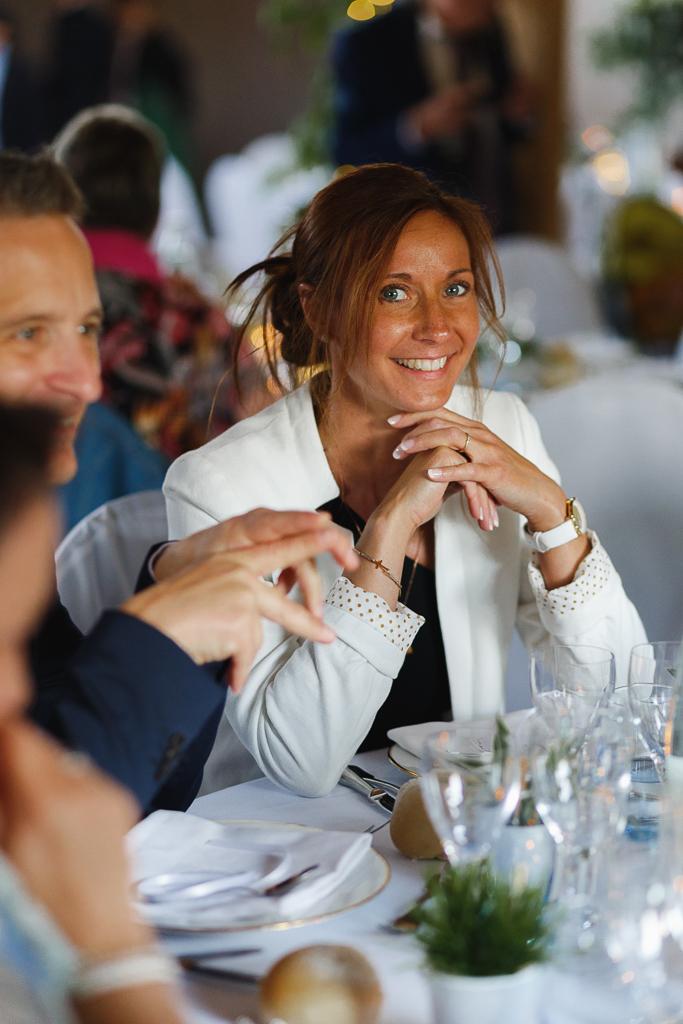 portrait à table invitée souriante salle de réception mariage de Bellebrune