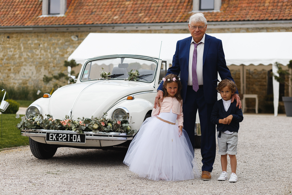 portrait homme fille et garçon d'honneur avec coccinelle décoration florale mariage cour ferme