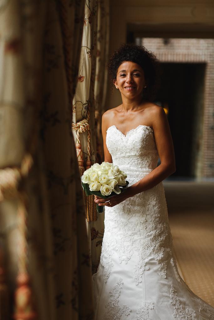 mariee avec bouquet de roses blanches dans couloir mariage au domaine de la chartreuse a gosnay