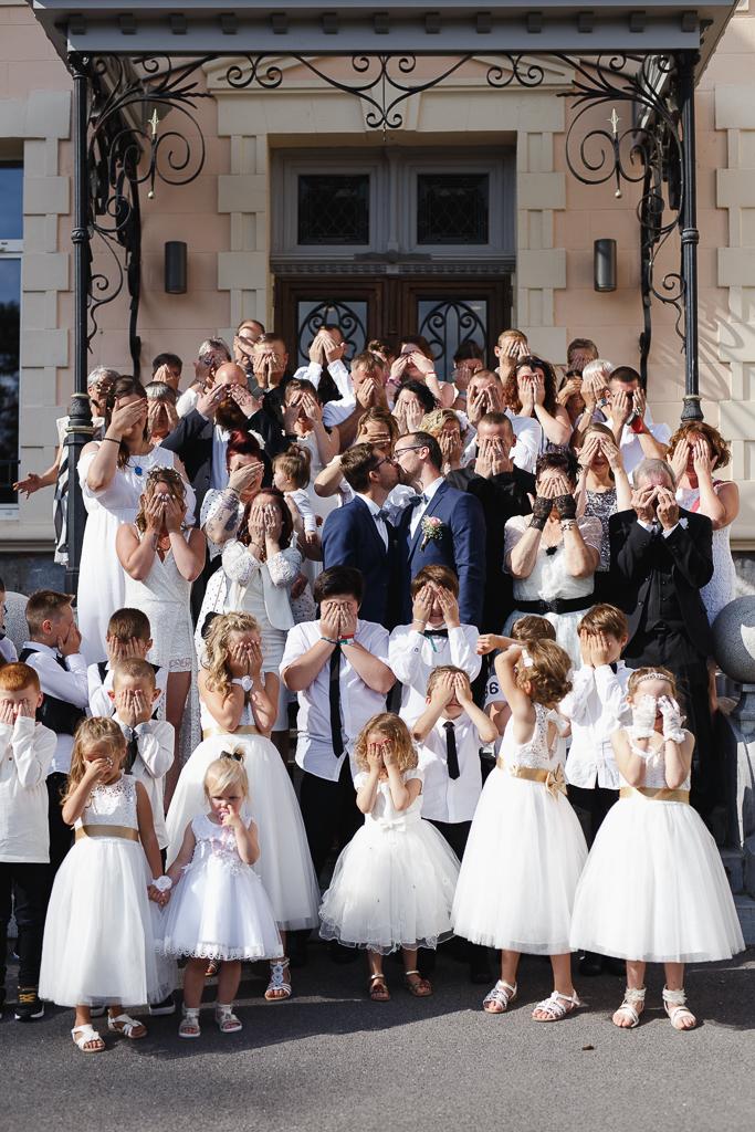 bisou mariés au milieu de tous les invités se cachant les yeux photographe mariage Fourmies Hauts-de-France