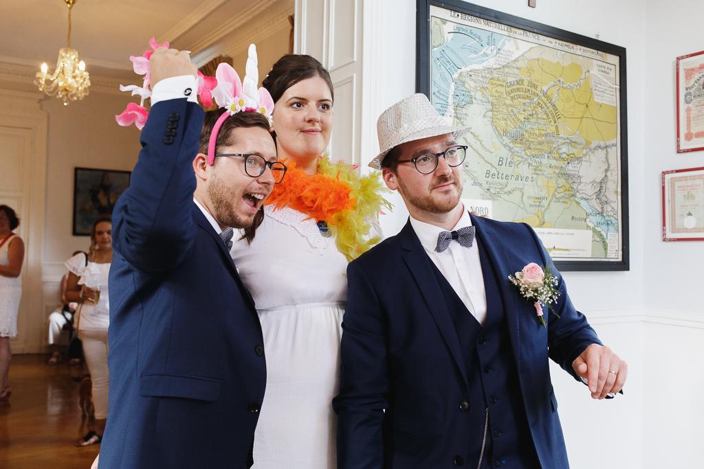 mariés et temoin déguisés posent devant photobooth mariage au château Nord