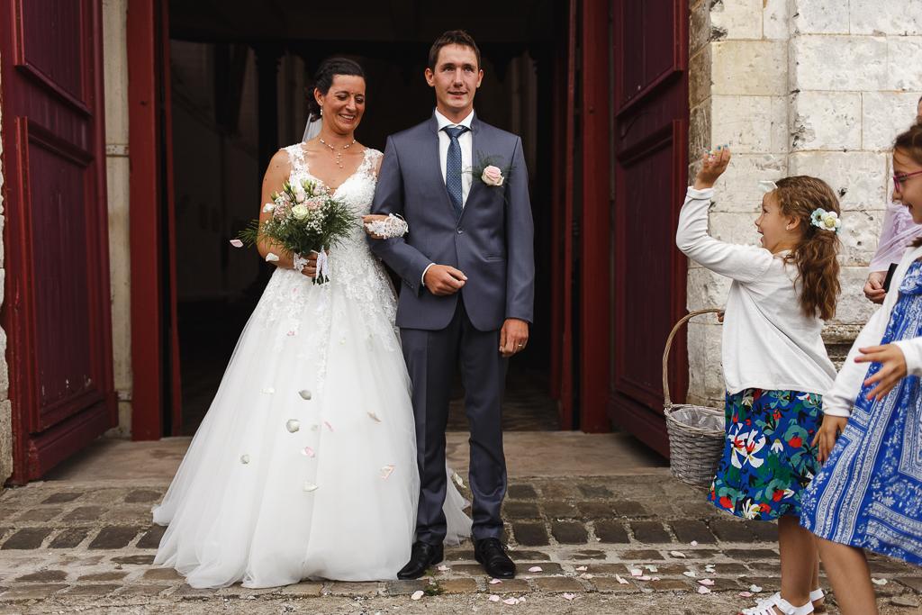 demoiselles d'honneur avec paniers lancent pétales de roses sur jeunes mariés sortie église Licques