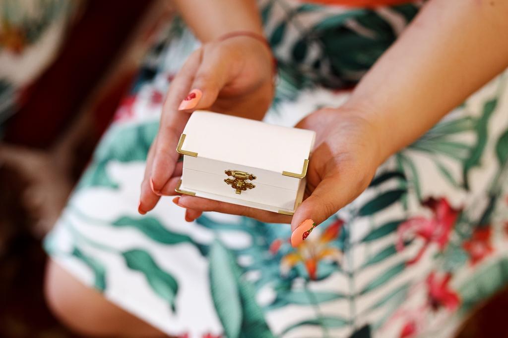 zoom sur boîte blanche renfermant les alliances dans mains de témoin mariage Nord