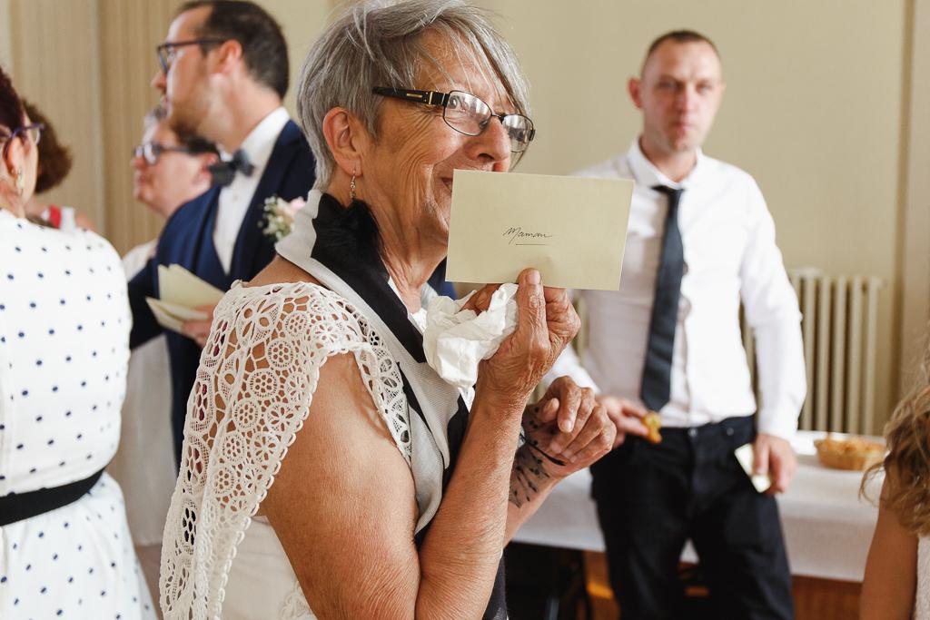 invitée tenant enveloppe surprise indiquant lieu de réception reportage mariage Hauts-de-France