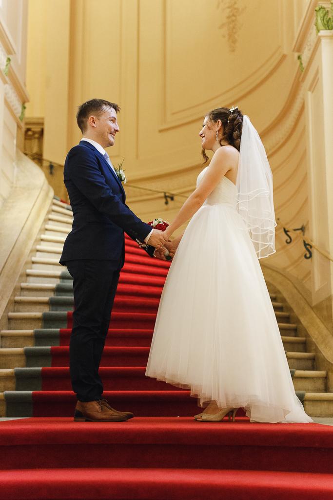 jeunes mariés gros sourire face à face escalier tapis rouge Fred Laurent photographe professionnel Nord