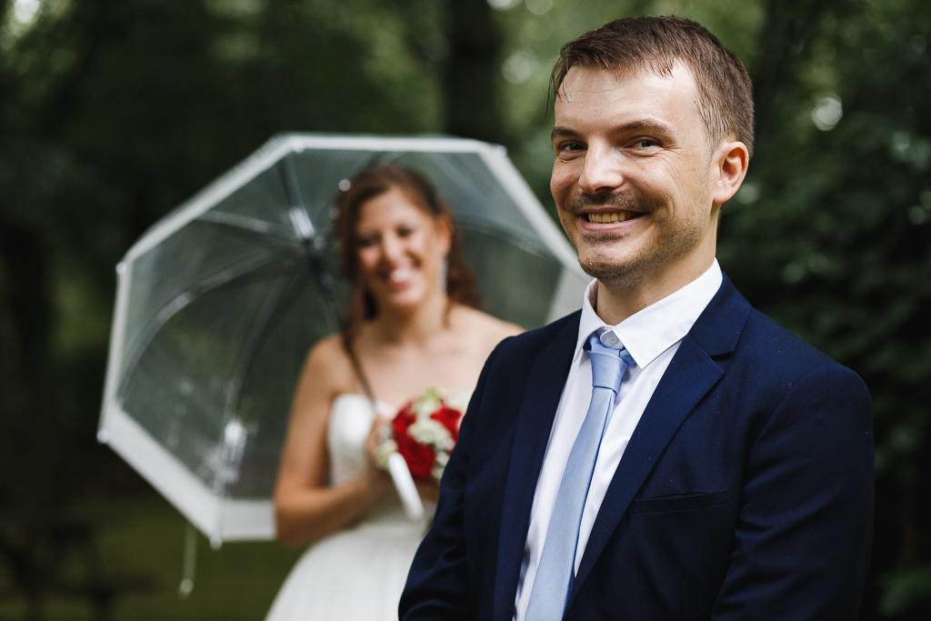 séance couple mariage Marcq en Barœul portrait du jeune marié avec mariée sous parapluie transparent en arrière-plan