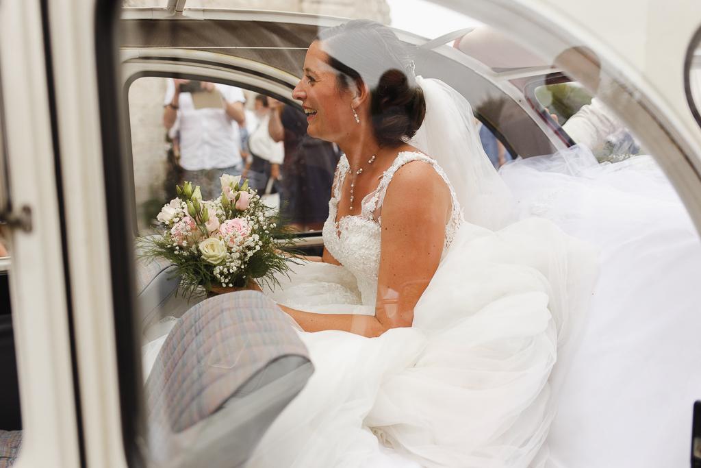 mariée avec bouquet de roses dans 2CV photographe mariage professionnel Fred Laurent Lille Côte d'Opale Hauts de France