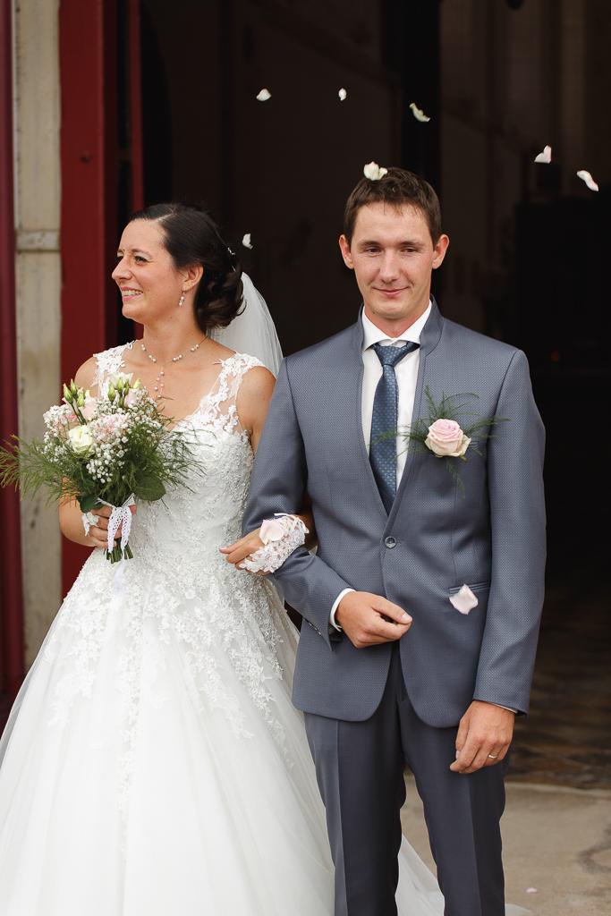 couple à la sortie de l'église pétales de roses mariage Trois Pays
