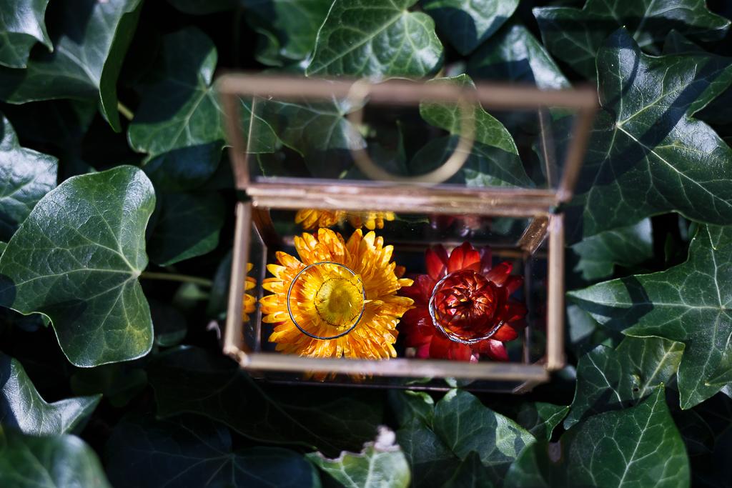 Coffret en verre bagues de mariages et fleurs.