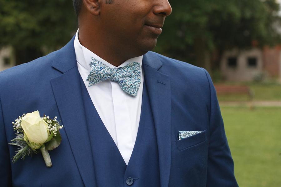 détail costume marié bleu noeud papillon et pochette liberty tons bleus boutonnière rose jaune pâle gypsophile et chardon