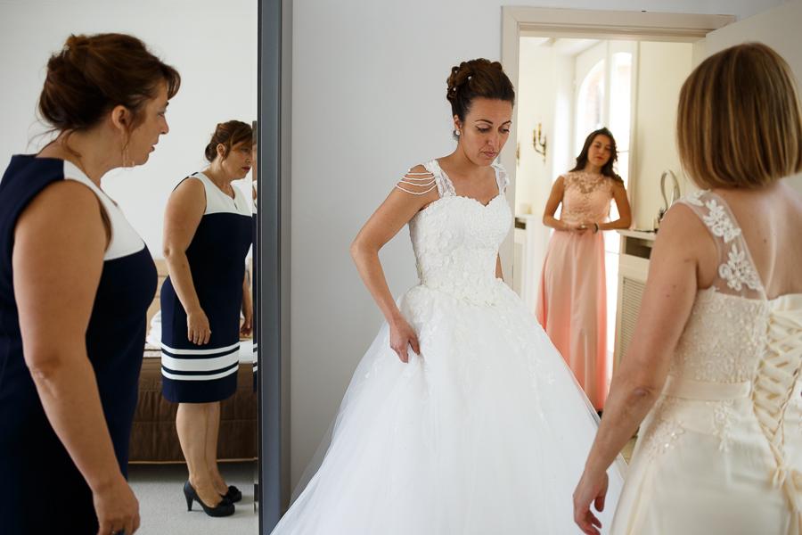 habillage de la mariée entourée de proches Fred Laurent photographe mariage Wambrechies Lille Nord