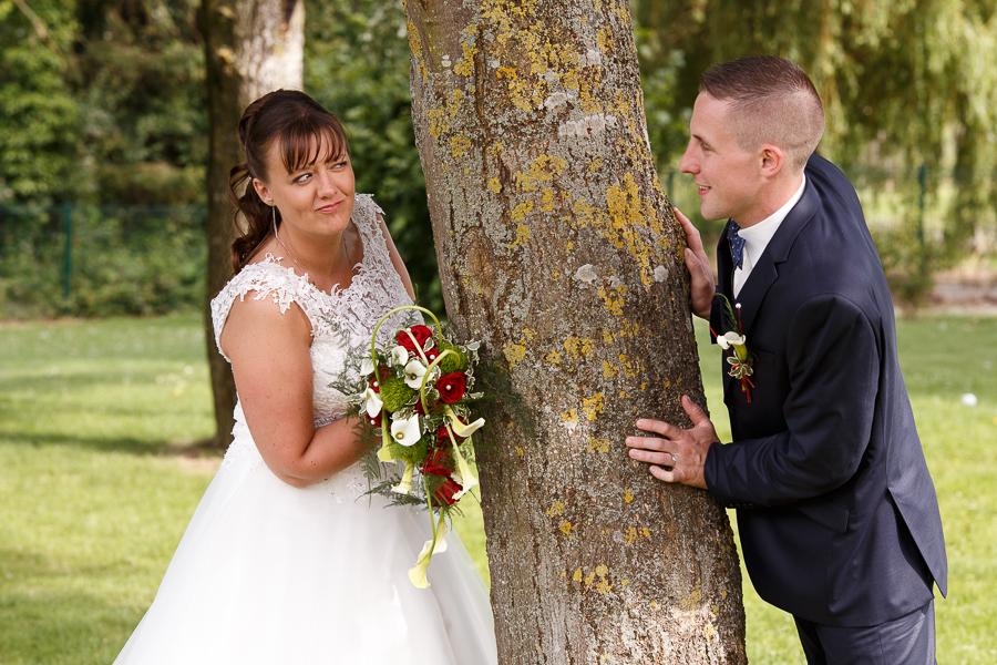 photo couple parc mariés jouent à cache cache autour d un arbre mariage à la campagne photographe mariage Nord Béthune La Bassée Hauts de France