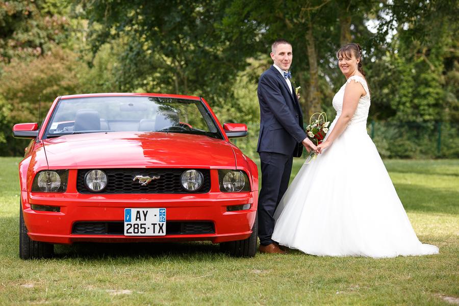 portrait couple mariage en mustang rouge séance couple photographe mariage à la campagne proche Béthune La Bassée